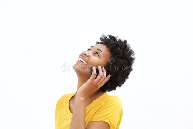愉快的年轻非洲妇女谈话在手机 免版税库存照片