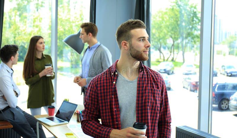 愉快的attracive年轻商人饮用的咖啡在办公室 免版税图库摄影