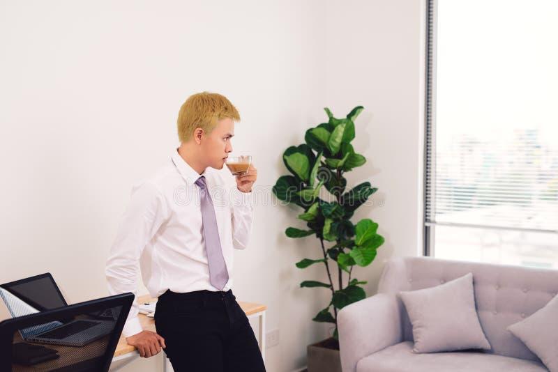 愉快的attracive年轻商人饮用的咖啡在办公室 库存照片