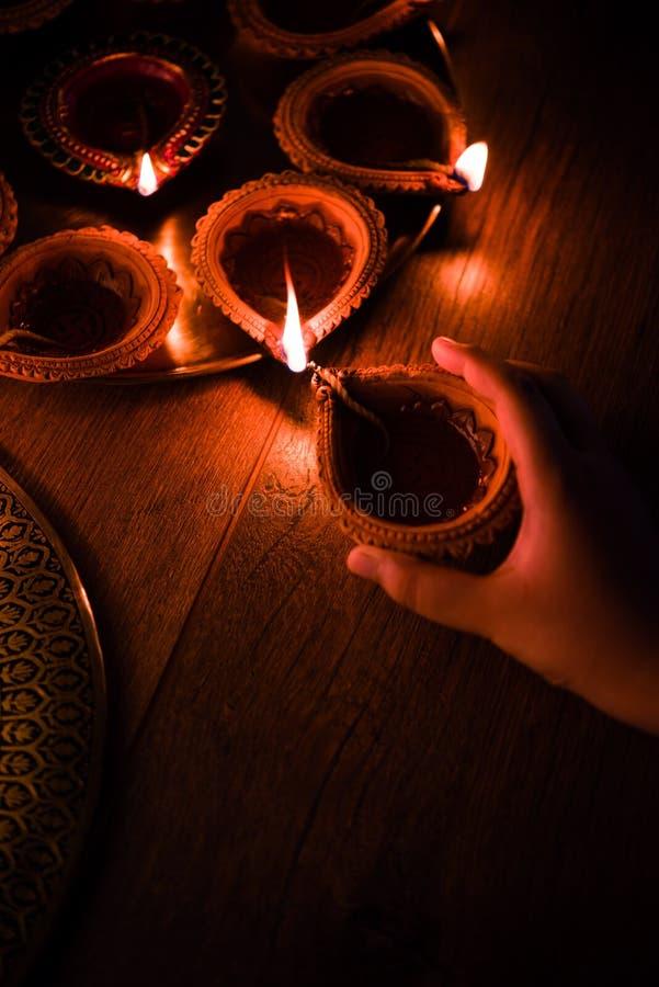 愉快的diwali -递举行或照明设备或者安排diwali diya或黏土灯 库存图片