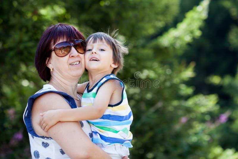 愉快的grandsonm画象,拥抱祖母户外 免版税库存照片