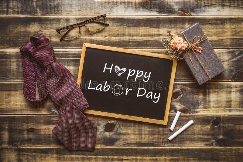 愉快的Labor';s天概念 礼物盒、领带、玻璃和黑板的平的被放置的图象有愉快的劳动节文本的 免版税库存照片