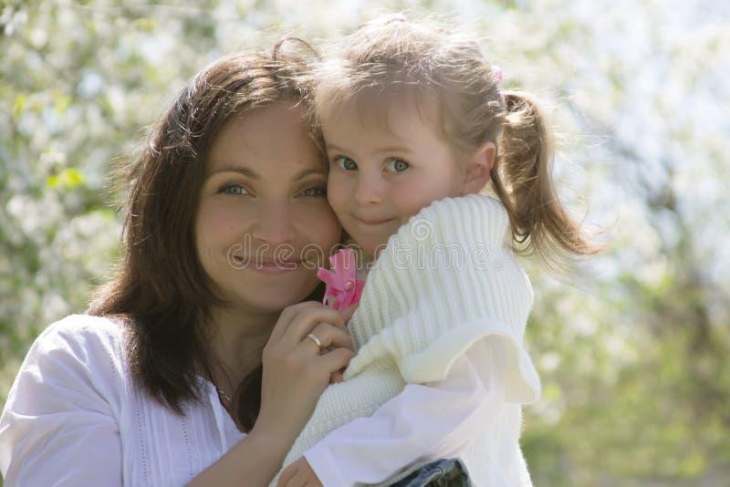 愉快的mothre和女婴在庭院里 免版税库存照片
