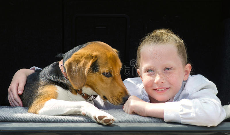 愉快的smilling的小女孩和小猎犬小狗 免版税库存图片