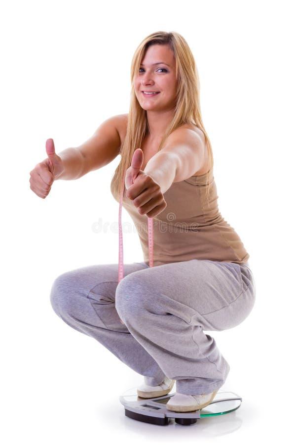 愉快的squating在称量器的妇女佩带的田径服 图库摄影