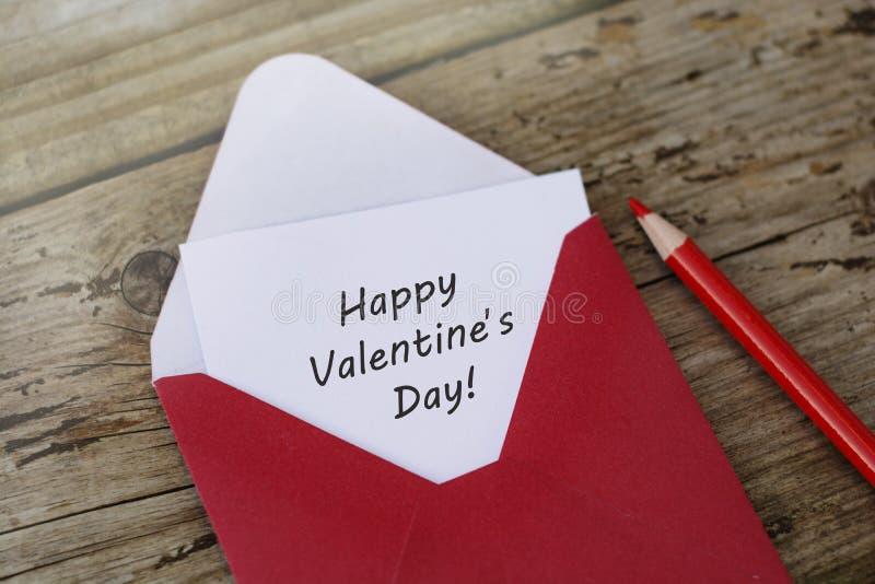愉快的Valentine';s天题字-与空插件的红色信封在与拷贝空间和红色铅笔的木背景 库存图片