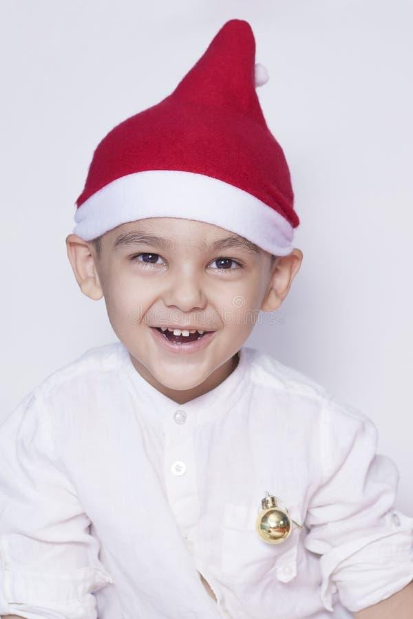 愉快矮小的个圣诞节男孩 庆祝圣诞节 6-7与圣诞老人帽子的岁孩子 免版税库存照片