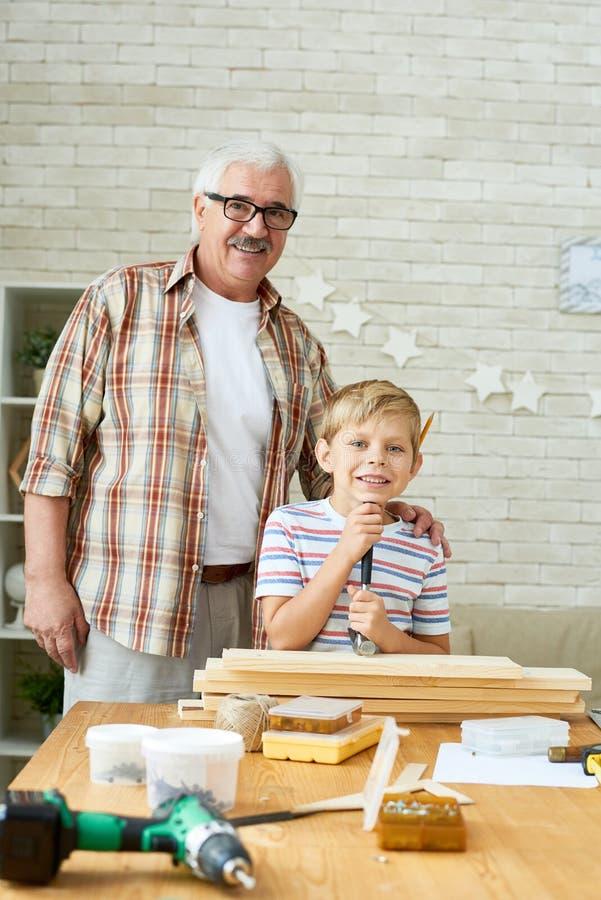 愉快祖父摆在与逗人喜爱的孙子 库存照片