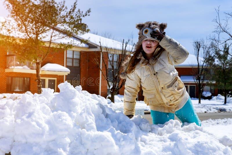 愉快笑的小女孩佩带的使用和跑在一个美丽的多雪的冬天公园 免版税库存照片
