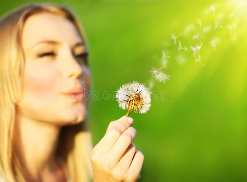 愉快美丽的吹的蒲公英的女孩 免版税库存图片