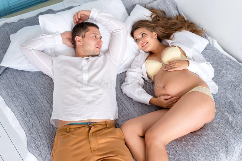 愉快美好的怀孕的夫妇一起期待孩子 男人和妇女说谎在床上的白色希腊样式卧室内部的 图库摄影