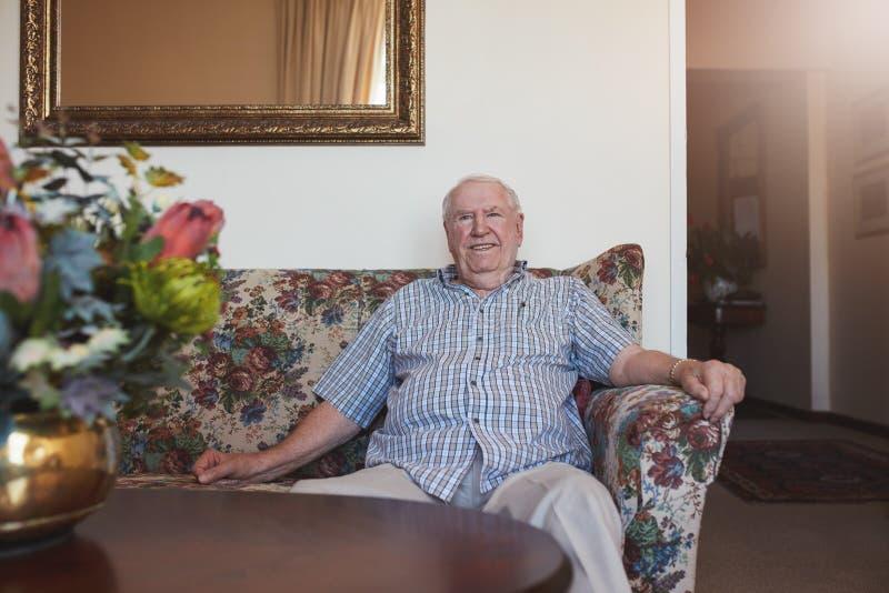 愉快老人坐在长沙发放松了 库存图片