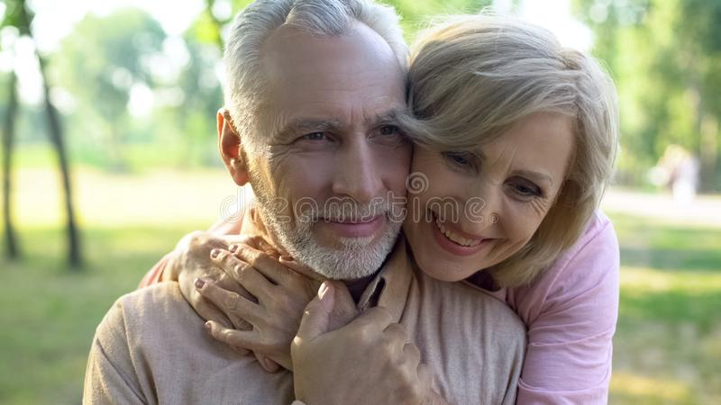愉快老夫妇拥抱,一起休息在公园,祖父母严紧 库存照片