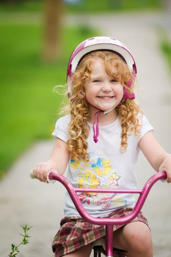 愉快自行车的女孩她 免版税库存图片