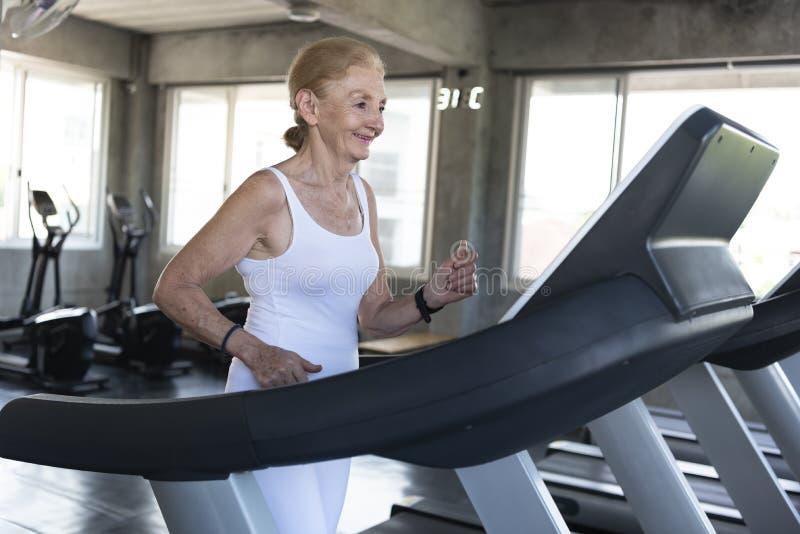 愉快资深的妇女行使跑步在健身房健身微笑和 年长健康生活方式 免版税库存照片