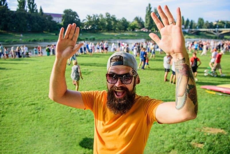 愉快遇见您 供以人员在人群人挥动的手绿色河沿背景前面的有胡子的行家 都市事件 免版税库存照片