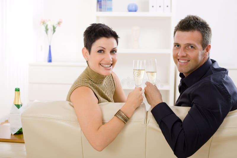 愉快香槟使叮当响的夫妇 库存照片