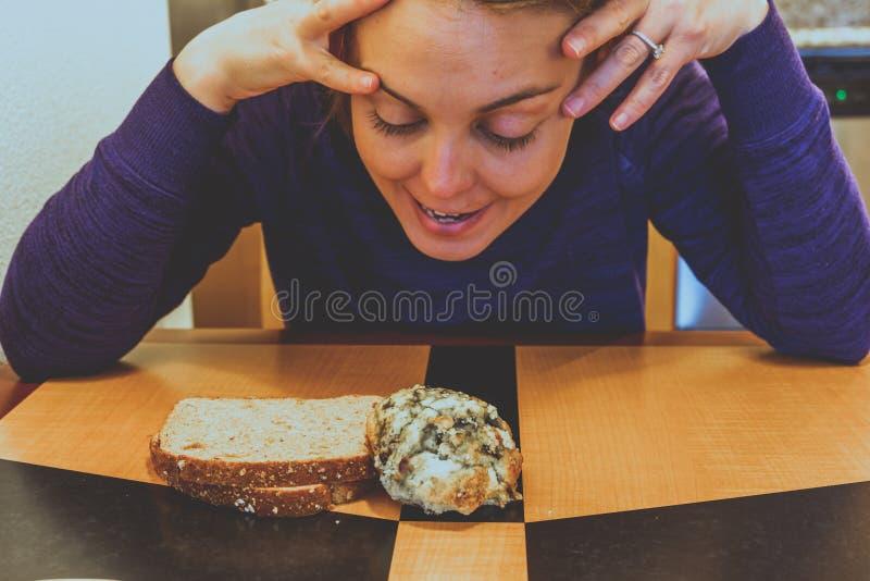 愉快,并且未定的年轻妇女决定在蓝莓烤饼或一片多士之间早餐,当坐在桌上时 免版税库存图片