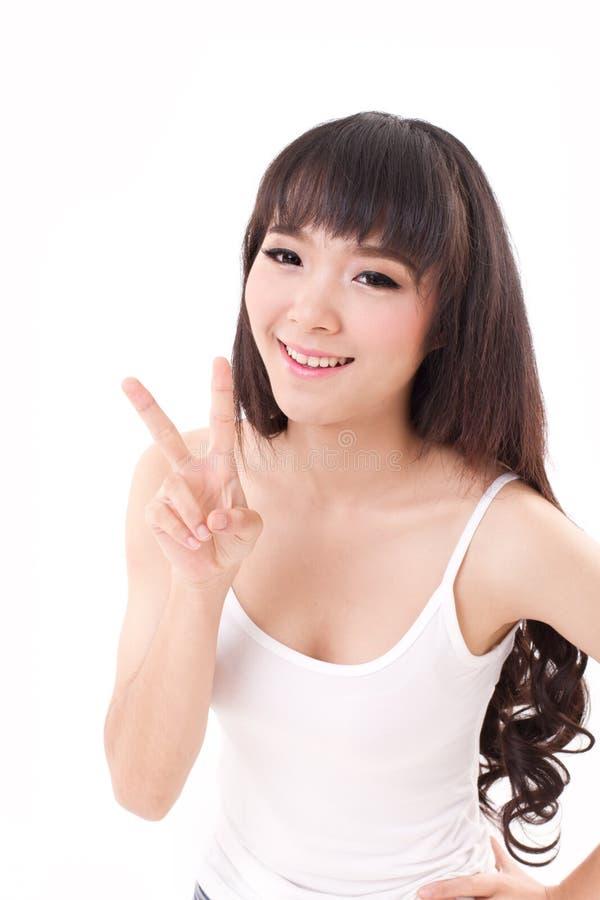 愉快,微笑的妇女上升,指向两手指,胜利 免版税库存照片