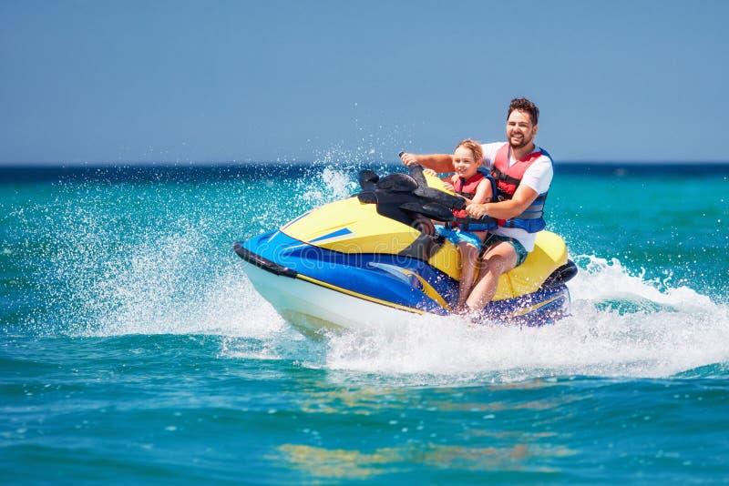 愉快,激动的家庭、父亲和儿子获得在喷气机滑雪的乐趣暑假 免版税库存图片