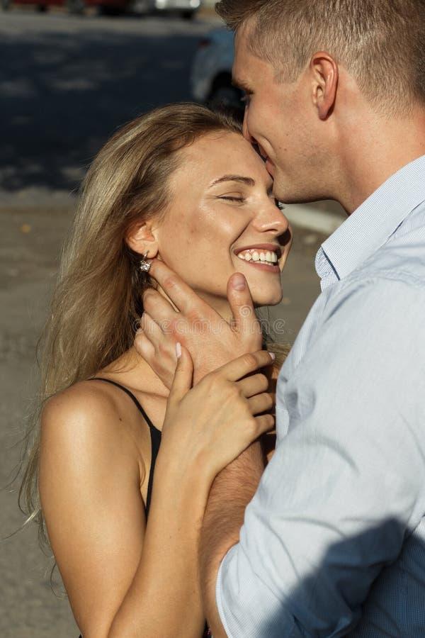愉快,爱恋夫妇拥抱 人亲吻女孩,保护 保护 图库摄影