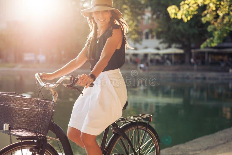 愉快年轻女性循环由池塘 免版税库存图片