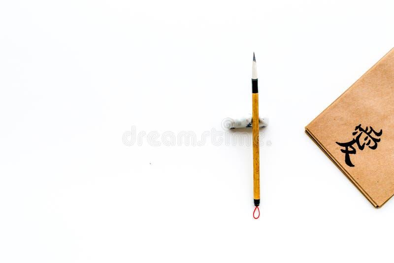 意味爱用英语的象形文字 在工艺纸笔记本的中国传统书法概念在专辑附近 免版税图库摄影