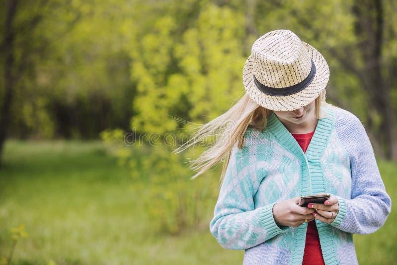满意和在手中微笑对手机的美丽的妇女和 免版税库存图片