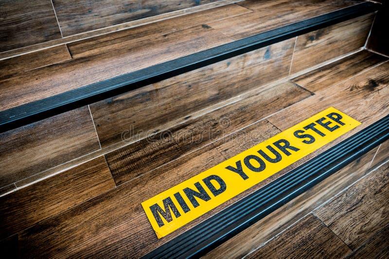 介意在木台阶黏贴的您的步贴纸标志 警告、摘要或者室内建筑学概念 库存照片