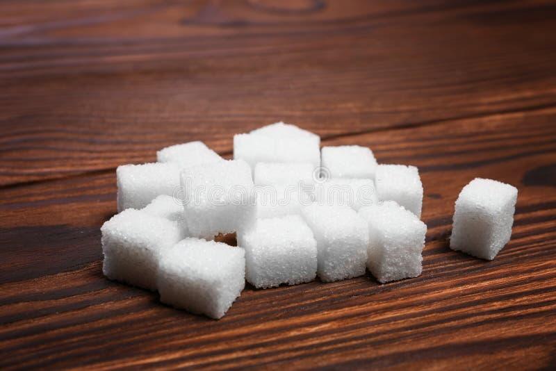 任意堆在一张黑褐色木桌上的甜糖立方体 在桌上的被提炼的白糖 糖立方体少量片断  库存照片