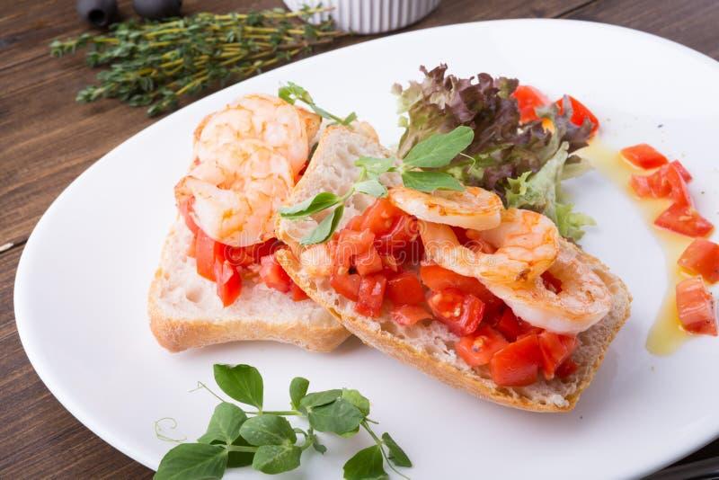 意大利三明治bruschetta用在白色板材供食的虾 免版税库存图片