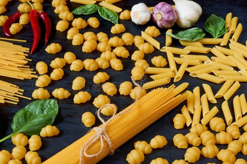 意大利传统食物、香料和成份烹调的作为蓬蒿,辣椒、大蒜和各种各样的面团在黑背景 免版税库存图片