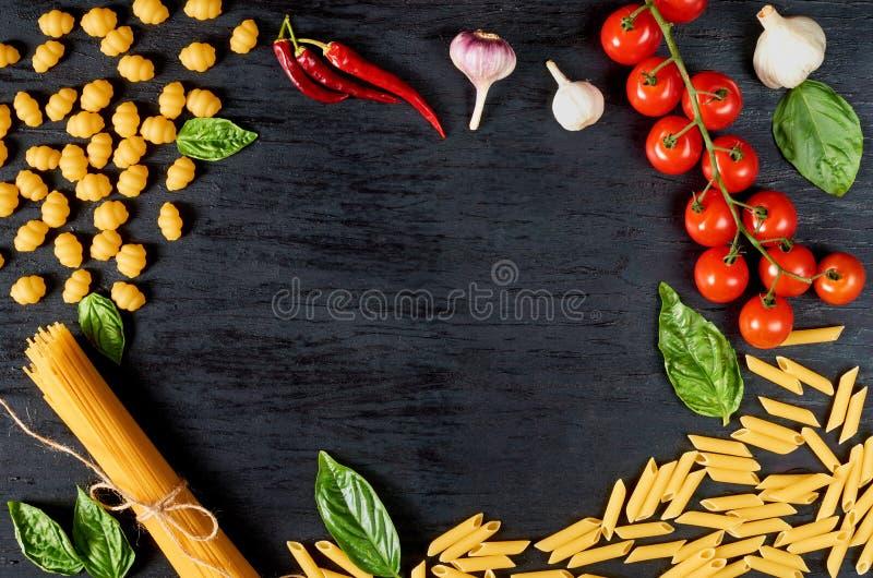 意大利传统食物框架、香料和成份烹调的,蓬蒿,西红柿、辣椒、大蒜和面团 免版税库存图片