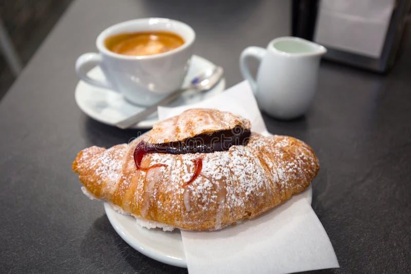 意大利咖啡用在桌上的果酱新月形面包 库存照片