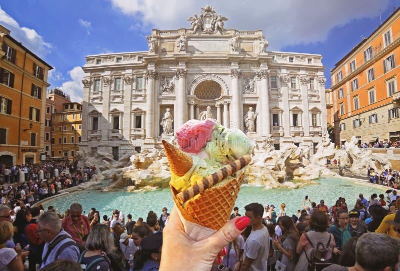 意大利圆锥形的冰淇淋杯在著名Trevi喷泉背景在手中举行了  免版税库存图片