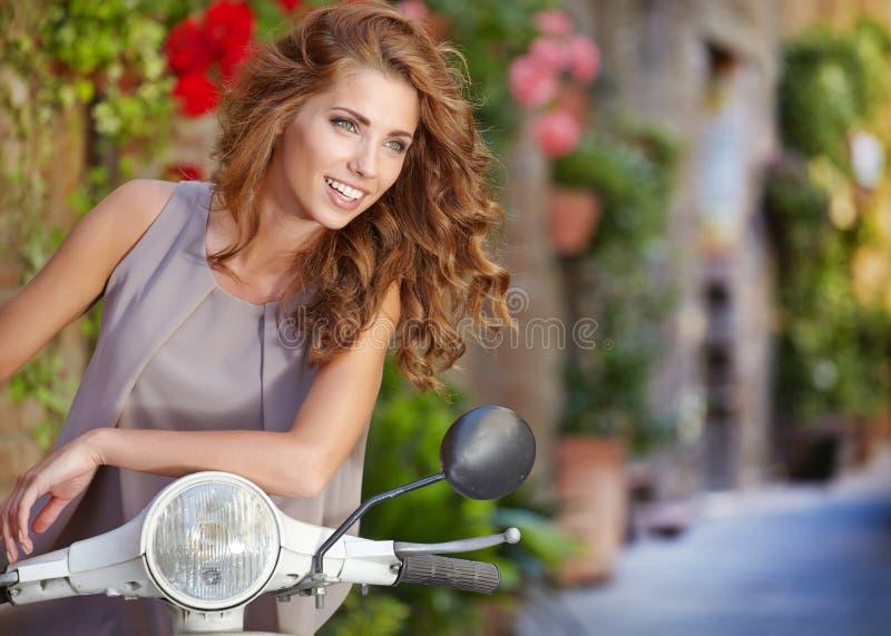 意大利妇女坐意大利滑行车 免版税库存图片