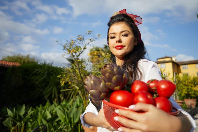 意大利妇女,主妇,收集晚餐的菜在家庭菜园 免版税库存图片