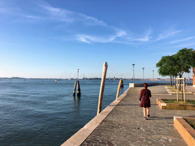 意大利威尼斯附近的穆拉诺岛,一个年轻的漂亮女人独自在海滨漫步。意大利威尼斯附近的穆拉诺å 图库摄影