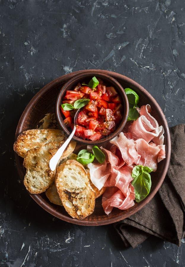 意大利开胃小菜-蕃茄bruschetta和熏火腿 可口快餐或开胃菜酒的 图库摄影