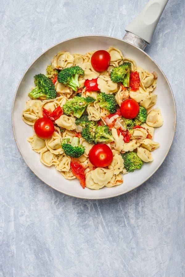 意大利式饺子用蕃茄和菜在白色煎锅,关闭调味  免版税库存图片