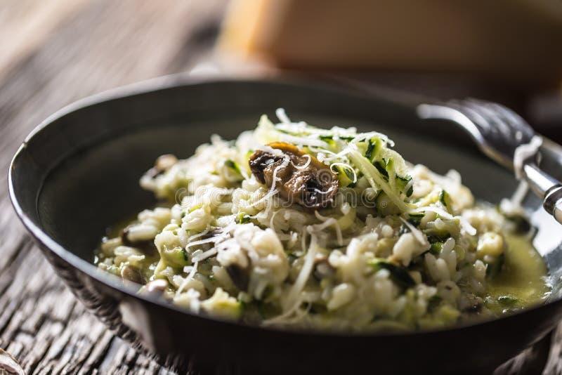 意大利意大利煨饭夏南瓜蘑菇和巴马干酪在黑暗的板材 免版税库存照片
