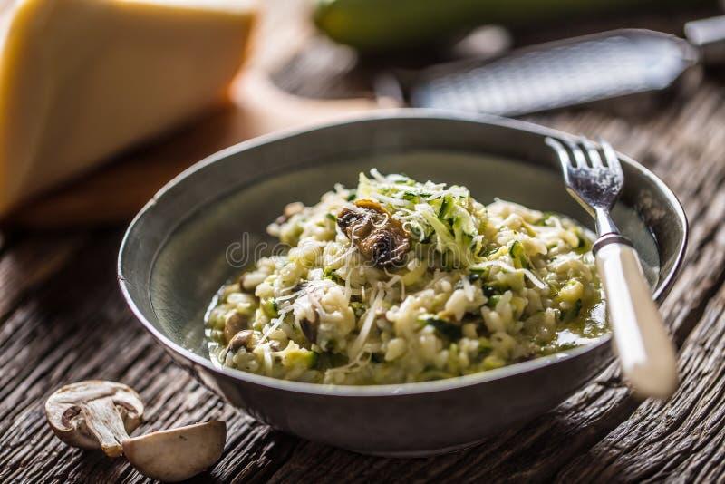 意大利意大利煨饭夏南瓜蘑菇和巴马干酪在黑暗的板材 图库摄影