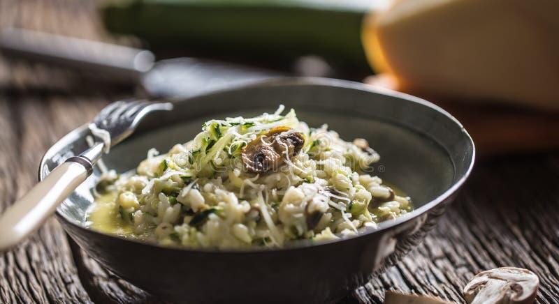 意大利意大利煨饭夏南瓜蘑菇和巴马干酪在黑暗的板材 免版税图库摄影