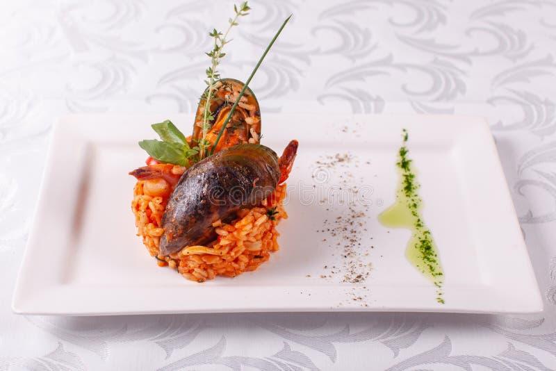 意大利意大利煨饭用海鲜,烤大虾,在壳的淡菜 西班牙肉菜饭 地中海餐馆菜单 库存图片