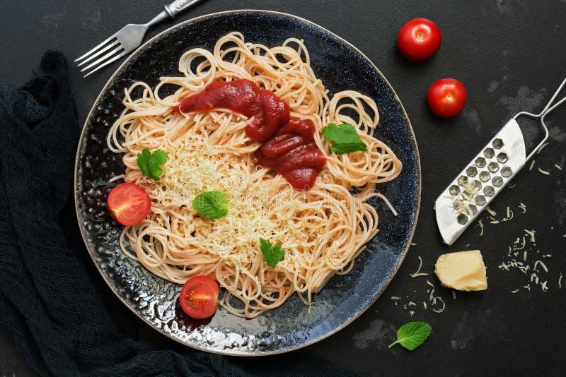意大利料理、传统面团意粉用西红柿酱,帕尔马干酪和绿色在黑石背景 观看从 库存照片
