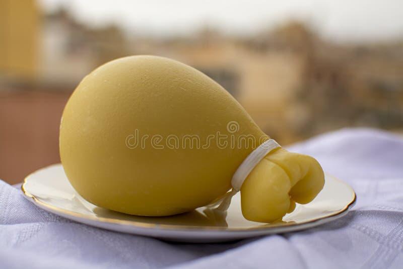 意大利普罗卧干酪caciocavallo在背景的老意大利镇变老了乳酪以与黄色houises的泪珠形式 免版税库存图片