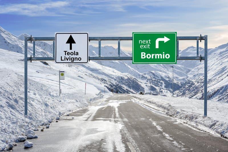 意大利滑雪镇博尔米奥和与很多雪和山天空的Teola和利维尼奥路大标志 库存照片