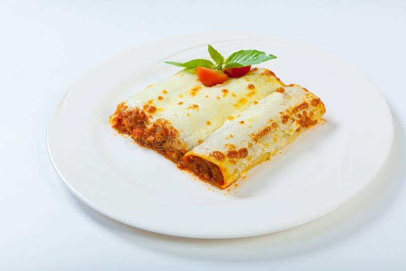 意大利烤宽面条在一块白色板材滚动 免版税图库摄影