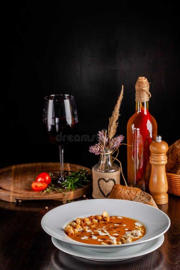 意大利烹调的概念 与橙色味道、鸡片断、面包油煎方型小面包片和奶油的南瓜奶油色汤 图库摄影