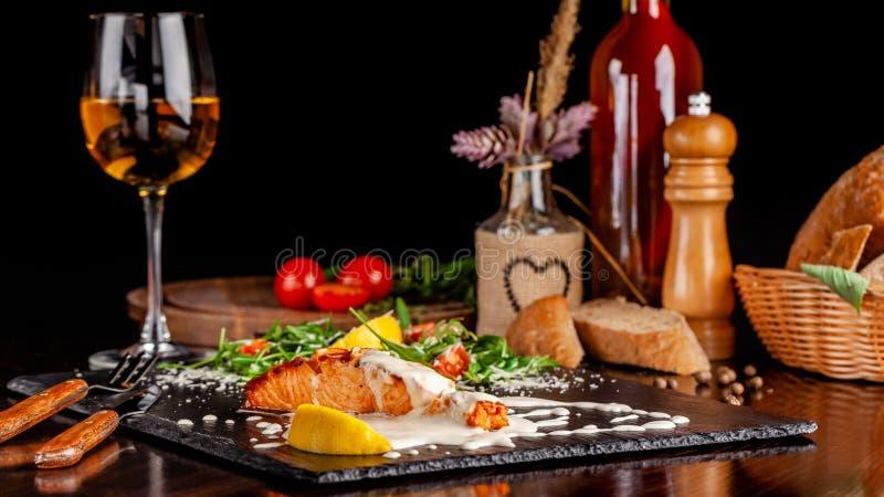 意大利烹调的概念 有芝麻菜、西红柿和帕尔马干酪的三文鱼内圆角在乳脂状的柠檬调味汁 库存图片